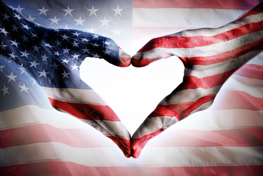 Memorial Weekend Tribute image with hands making a heart shape with an American flag background